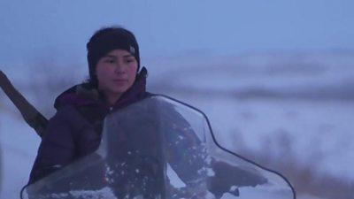A young woman riding a snow ski