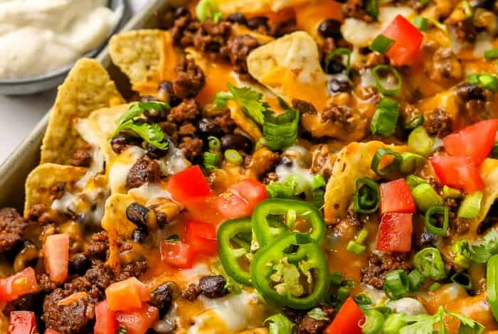 A tray full of baked nachos topped with ground beef, black beans, green onions, tomatoes, jalapenos and shredded cheese, with a side of salsa and sour cream
