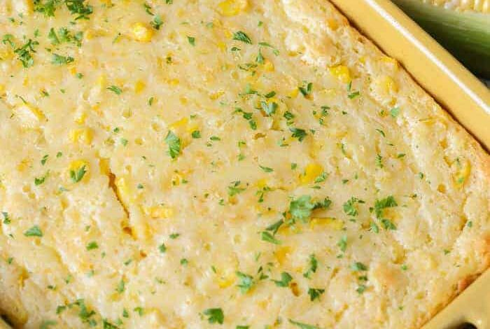 Yellow baking dish of Corn Casserole with ears of corn next to it