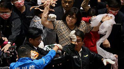 Taiwan lawmakers throw pork intestines at each other during a scuffle in the parliament in Taipei, Taiwan