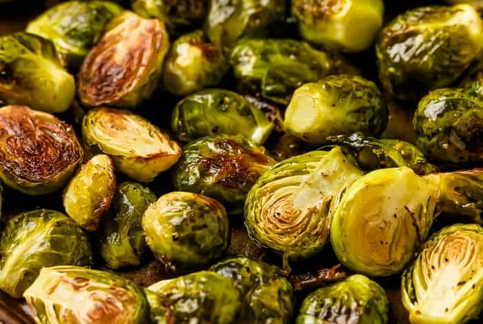 Baked, halved brussel sprouts, oiled and seasoned with pepper in a baking tray